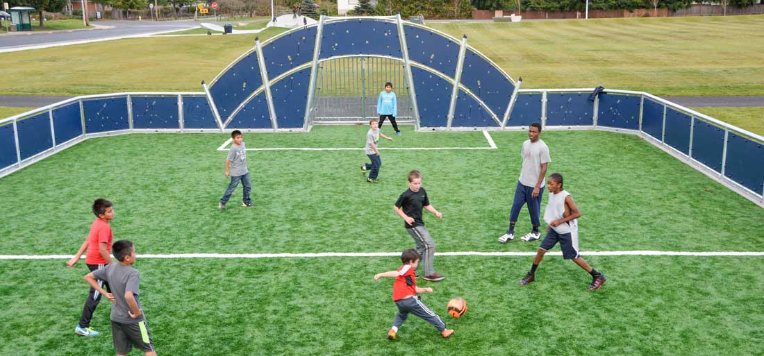 Children playing on a multi-sport court with safety surfacing