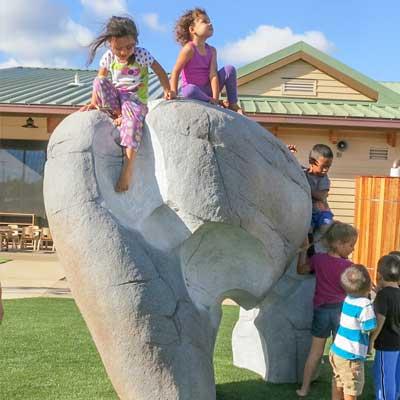 Children on IDS Rock Sculpture for playground