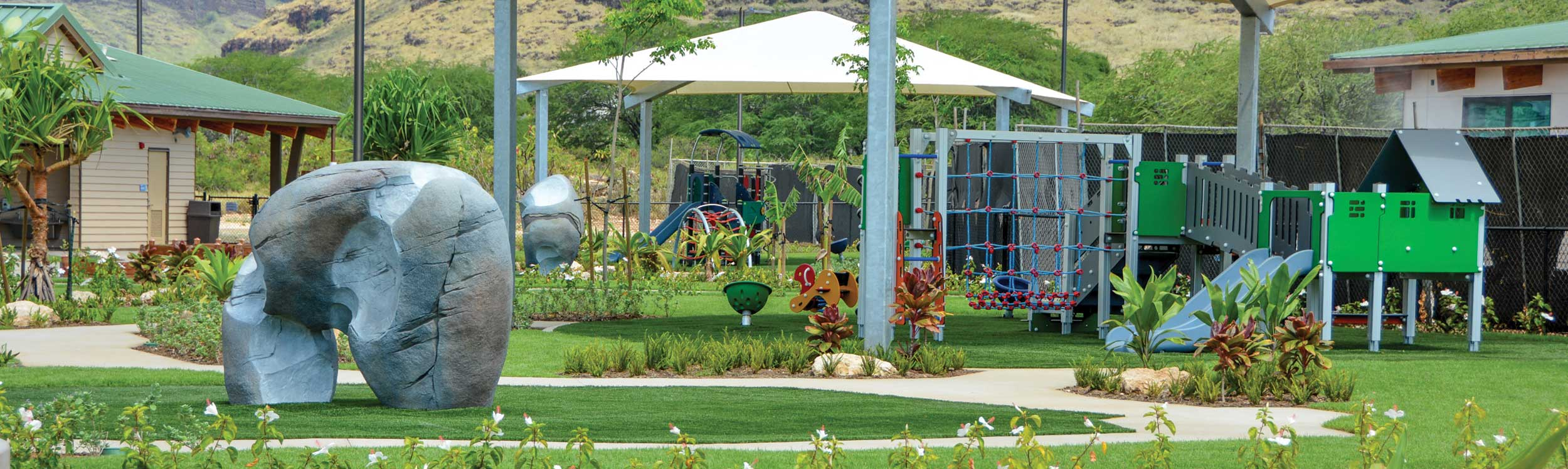Shade structure over play equipment with rock climbing toy