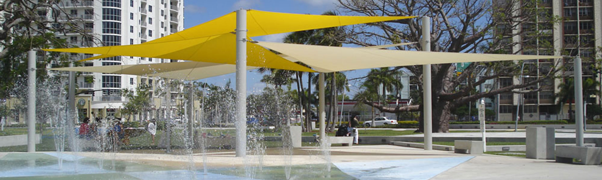 Shade structures for splash parks with sail features