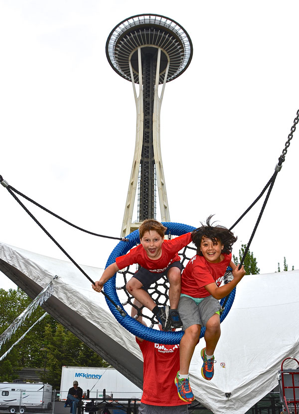 Boys swinging on the basket swing on the Seattle Center play structure